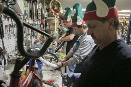 Men in elf hats work at tool bench
