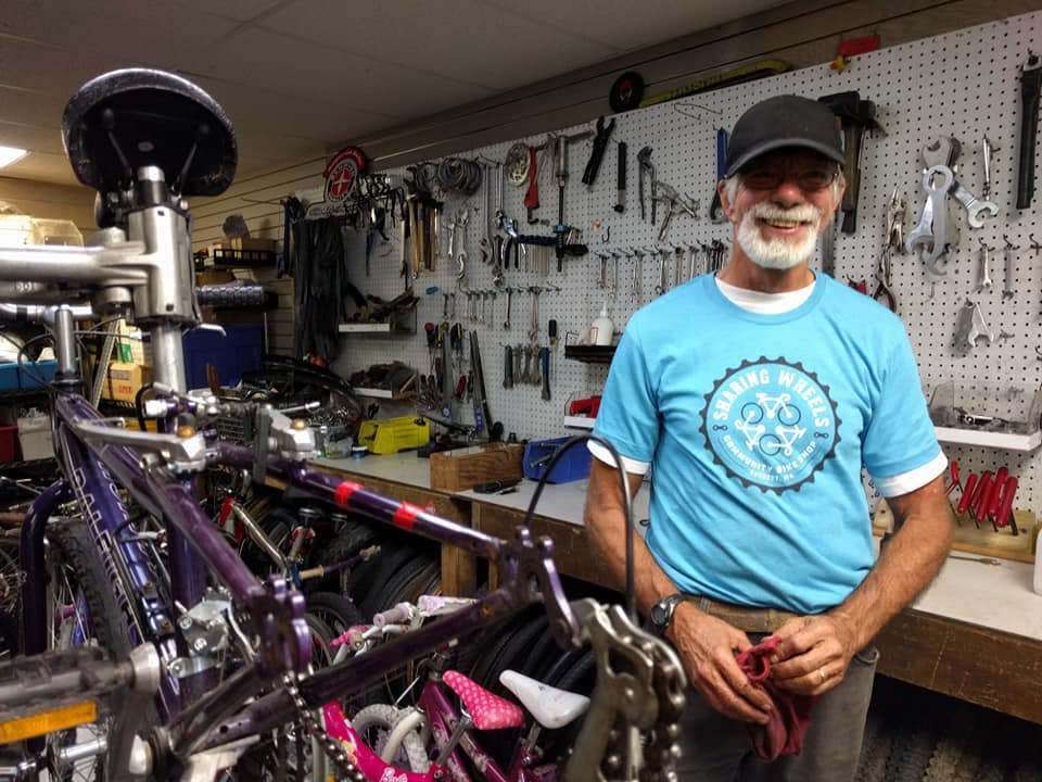 Man stands with bike tools in background