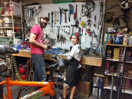 Josh and boy in an elf hat at tool bench