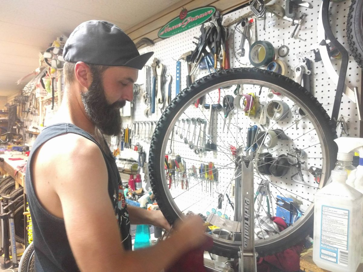 bike mechanic working to true a wheel