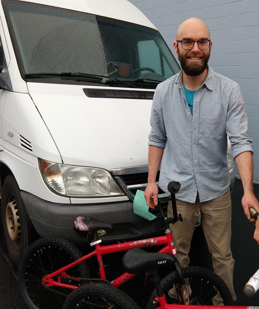 Scott with his van and a kids bike