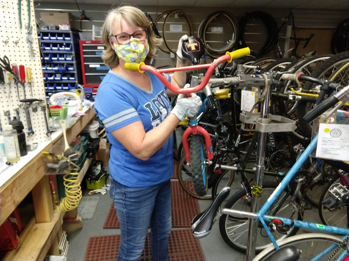 Woman wearing mask works on a children's bicycle