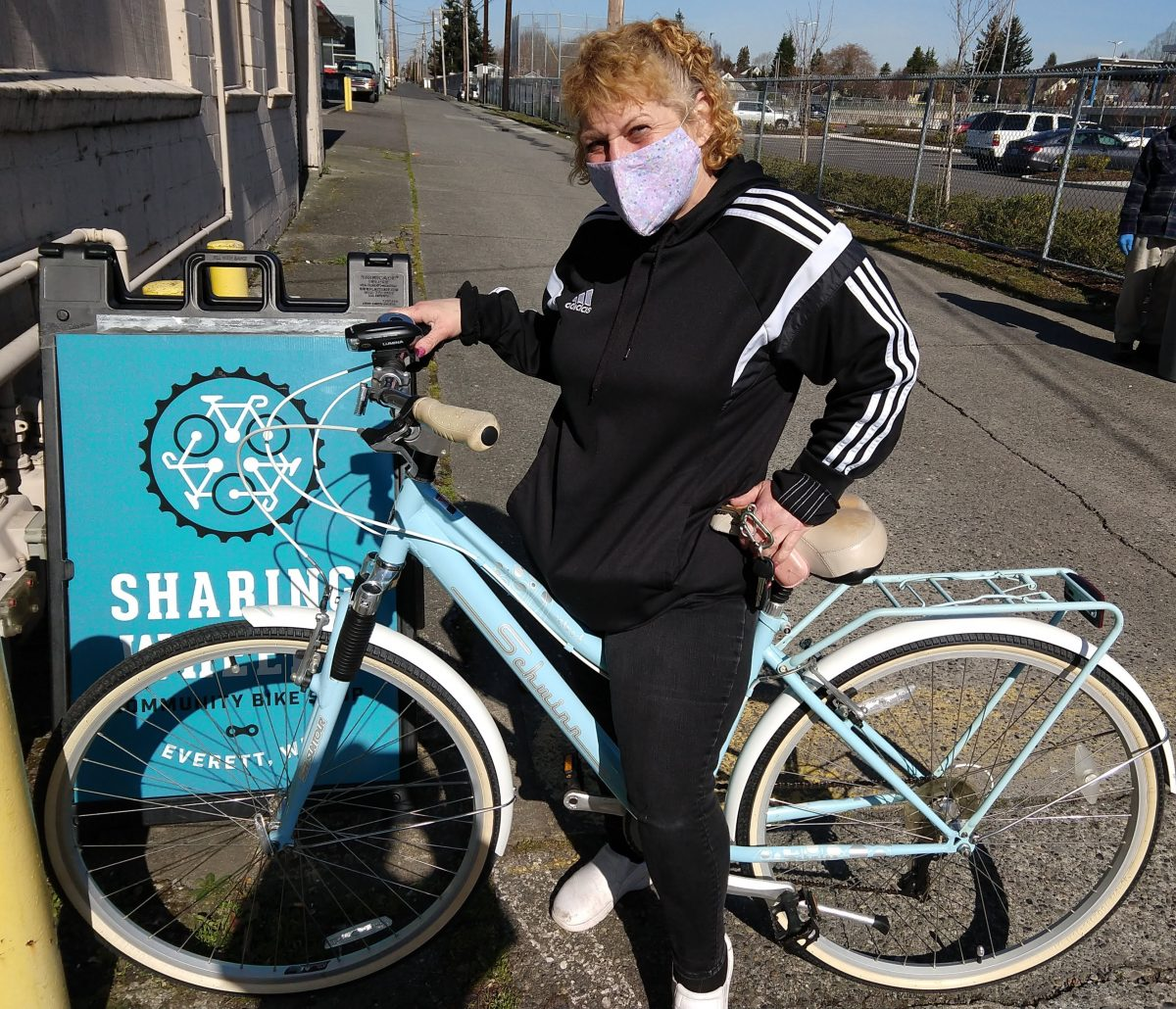 Woman on a cruiser bike smiles under her facemask
